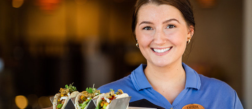 Waitress in a restaurant wearing a blue shirt and smiling